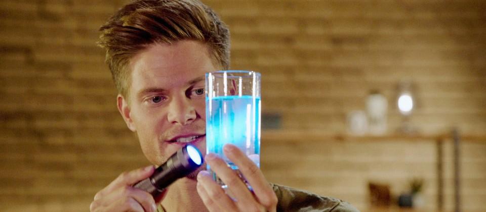 Gut zu wissen-Moderator Philip Häusser leuchtet mit Schwarzlicht-Lampe auf ein Glas Tonic