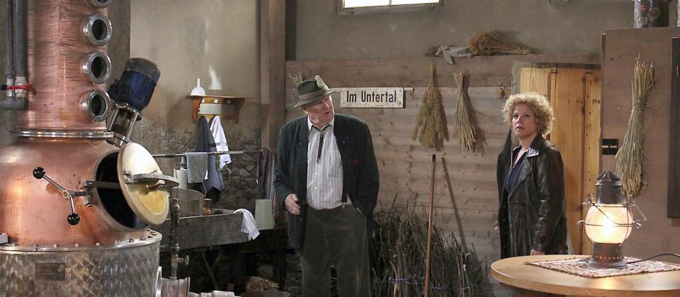 osef Zimmermann (Luis Lamprecht, li.) zeigt Bea (Christiane Brammer) seine Brennküch