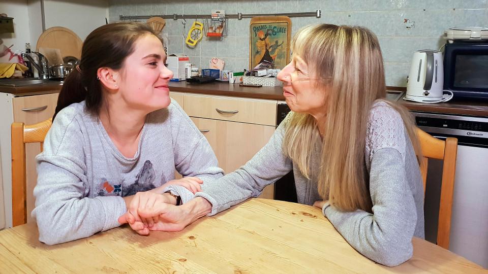Ein brünettes Mädchen und eine blonde Frau mit einem Schlauch in die Nase halten die Hände