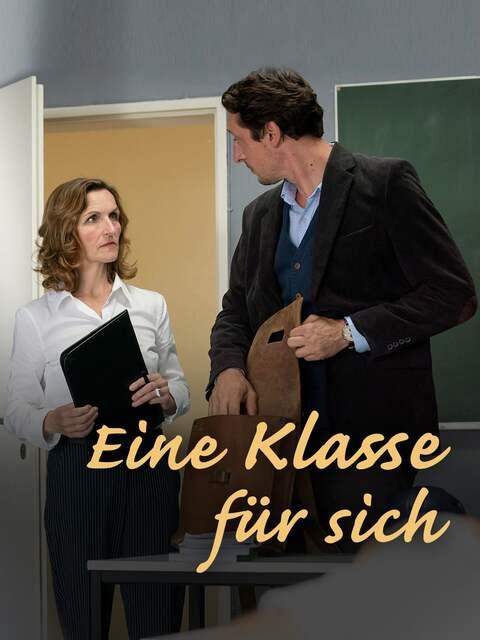 Fabian Sorge (Hans Löw) packt versehentlich am Lehrerpult aus, Lehrerin Frau Selb (Eva Mannschott) ist irritiert.