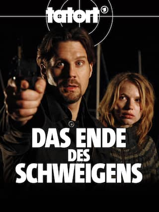 Claes Möller (Thomas Heinze) richtet eine Waffe auf jemanden. Neben ihm steht Maxi Rohwedder (Anna Brüggemann).