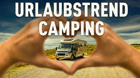 Hand formt Herz um einen Camper