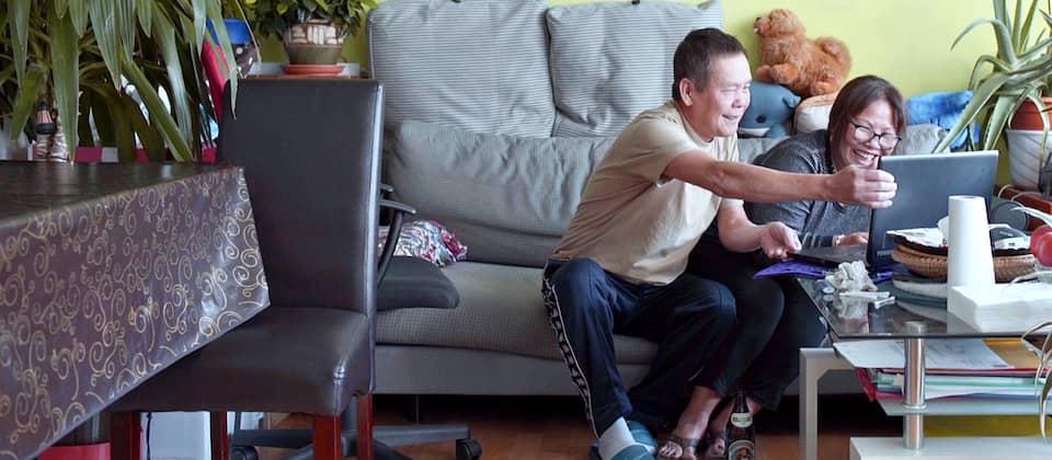 Tam und Bay auf ihrer Couch beim Skypen mit Freunden in der alten Heimat Vietnam.