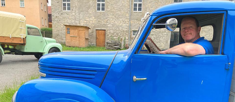 Ein Mann sitzt in einem Blauen Auto.