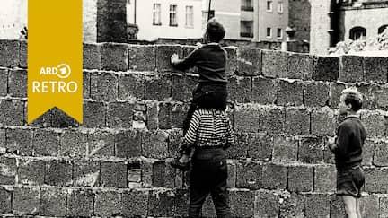 Drei Jungen an der Berliner Mauer.