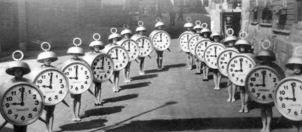 Frauen in Weckerkostümen stehen Spalier, schwarz-weiß Bild
