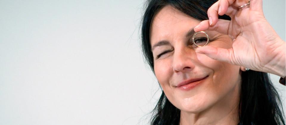 Hochzeitsplanerin Ines Wirth schaut durch einen Ehering.