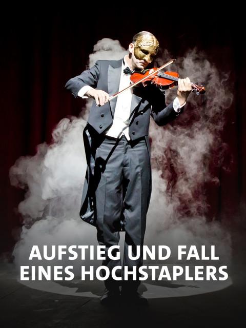 Ein maskierter Mann spielt Geige auf der Bühne
