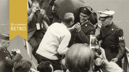 Elvis auf Gangway mit Seesack auf Schulter; umringt von Reportern und Journalisten, als er das Schiff verlässt.