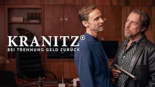 """Szenenbild aus der Impro-Serie """"Kranitz - Bei Trennung Geld zurück"""": Ein Mann mit Pistole und einer mit Sektflasche und Gläsern stehen in einem Zimmer."""