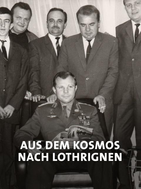 Kosmonaut Gagarin sitzt vor einer Gruppe Männer in Anzügen