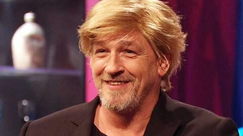 Ein Mann mit einer blonden Perücke grinst