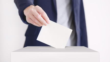 Ein Zettel wird in eine Wahlurne gesteckt