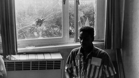 Ein mosambikanischer Vertragsarbeiter in seinem Wohnheimzimmer, im Hintergrund die eingeworfenen Fensterscheiben.