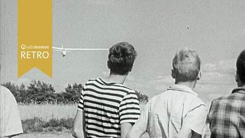 Ein paar Jungen beobachten, wie ein Segelflugzeug zur Landung ansetzt.
