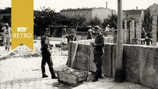 Grenzsoldaten und Arbeiter bei der Errichtung der Mauer